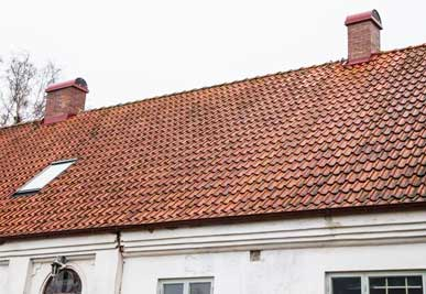 Montering av två röda skorstenshuvar i Billeberga, Skåne.